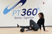 A woman uses a foam roller under her leg in a PT360 workout room