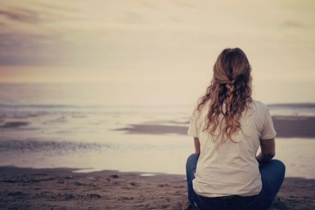 A woman sits cross legged on the beach looking out at the ocean