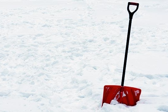 A photo of a red snow shovel standing in a snowy field