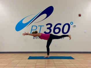 At a PT360 yoga class, a woman performs the warrior 3 pose.