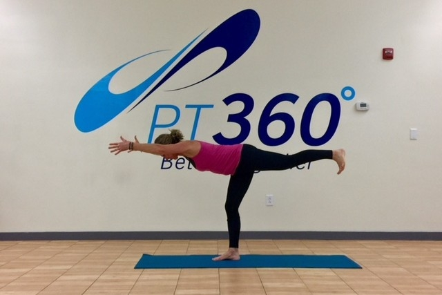 A woman does a yoga pose standing on one leg in a PT360 exercise room