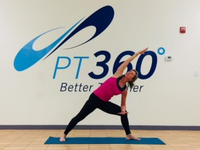 At a PT360 yoga class, a woman performs a side angle pose.
