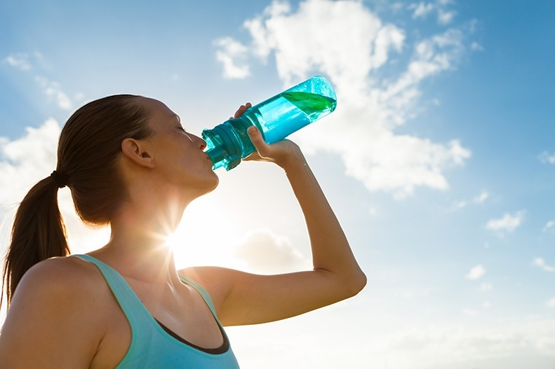 A woman drinks water out of a bottle