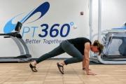 A woman does a stretching exercise in a PT360 studio