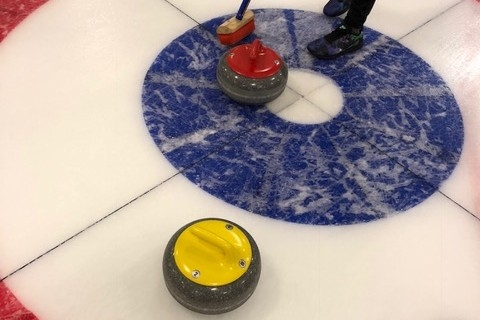 A curler poses with curling stones in an ice rink