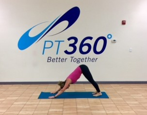 At a PT360 yoga class, a woman performs the down dog pose.