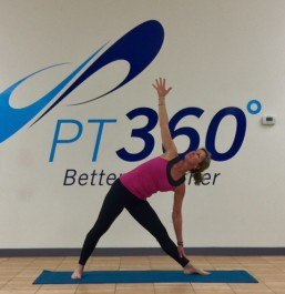 At a PT360 yoga class, a woman performs the triangle pose.
