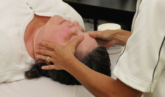 A physical therapist performs Craniosacral Therapy on a patient