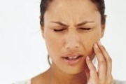 A woman with jaw pain winces winces and touches her cheek