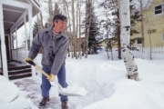 A photo of a man shoveling snow from the walk in front of a house