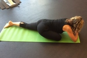 A woman does a yoga pose while lying on the floor