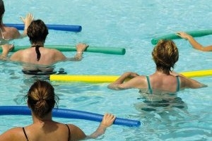 Patients in the aquatic therapy pool exercise with pool equipment