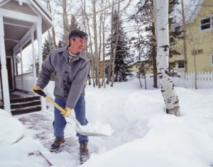 A photo of a man shovelling snow.